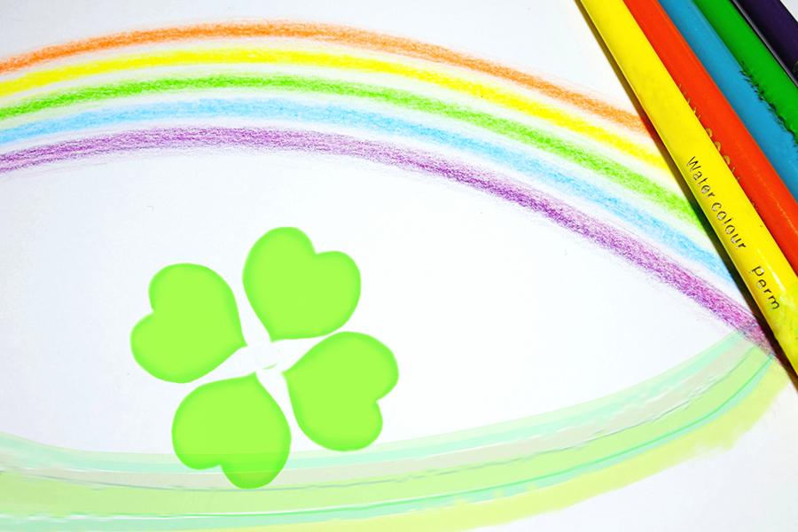 色鉛筆で描かれた虹とクローバー